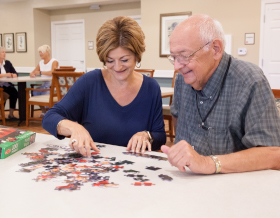 two-smiling-people-work-on-a-jigsaw-puzzle-together